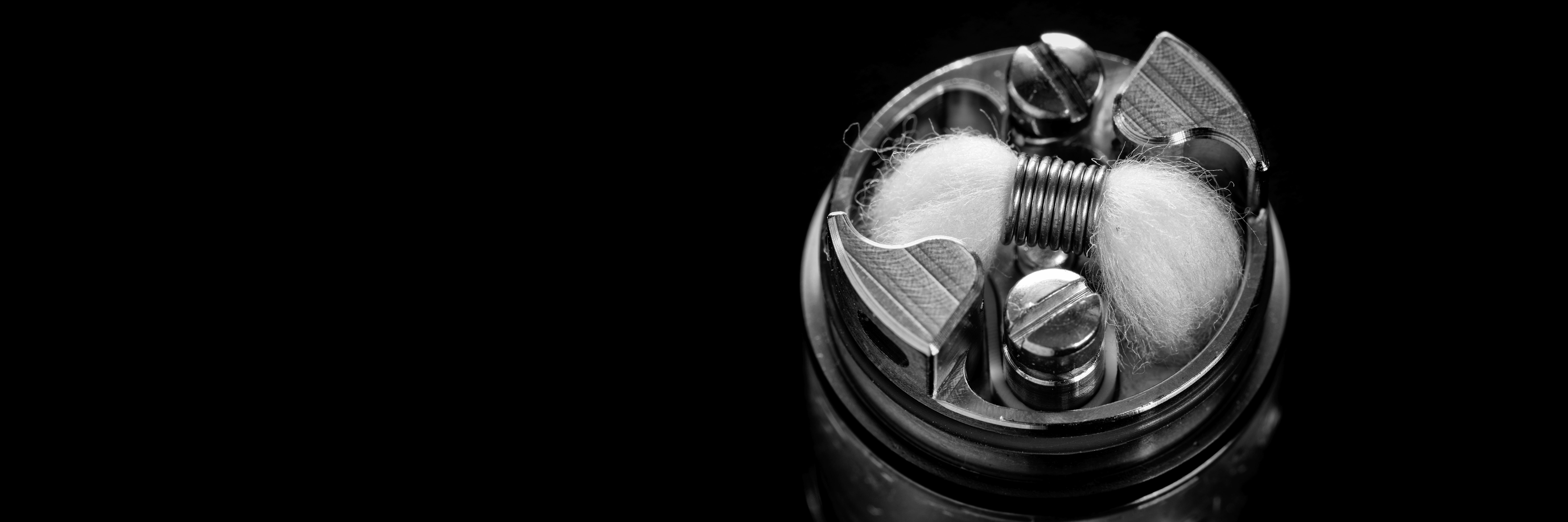 black and white, monochrome shot of single micro coil with japanese organic cotton wick in high end rebuildable dripping tank atomizer for flavour chaser, vaping device, vape gear, vaporizer equipment